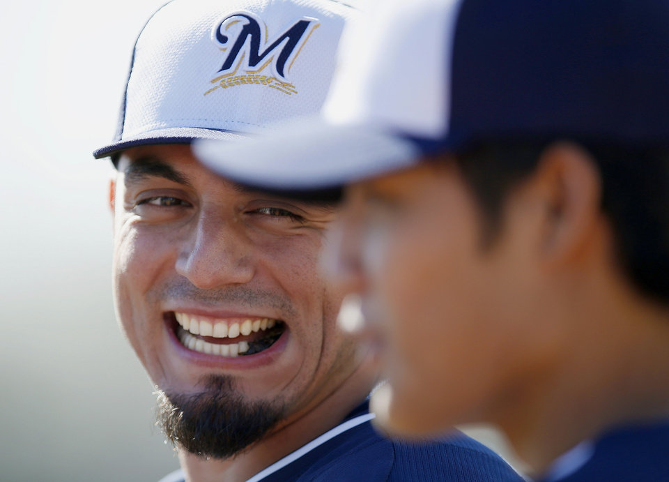 Photo - Milwaukee Brewers' Matt Garza, left, laughs as he tries to talk to teammate Wei-Chung Wang, of Taiwan, during spring training baseball practice, Monday, Feb. 17, 2014, in Phoenix. (AP Photo/Ross D. Franklin)