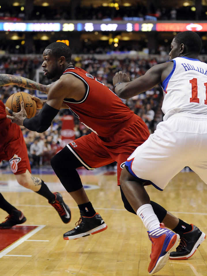 Miami Heat's Dwyane Wade, left, drives past Philadelphia 76ers' Jrue Holiday (11) during the first half of an NBA basketball game, Saturday, Feb. 23, 2013, in Philadelphia. (AP Photo/Michael Perez)