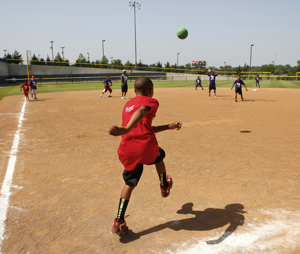 YOUTH KICKBALL TOURNAMENT / CHILD / CHILDREN / KIDS: A McKinley Park Shooters player kicks the ball high toward the defenders from Pitts Center. Kickball tournament at Hall of Fame Stadium Wednesday, June 26, 2013. Sponsored by the OKC Parks and Recreation Department and hosted by the Police Athletic League. Photo by Jim Beckel, The Oklahoman.