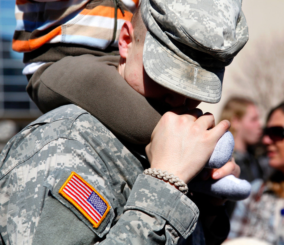 Photo - SPC Aubrey Lindley of Bixby, OK, kisses the leg of his 15-month-old son, Treyton, who sits on his dad's shoulders, after the 45th Infantry Brigade Combat Team Deployment Ceremony in downtown Oklahoma City, Wednesday, Feb. 16, 2011. This will be Lindley's first deployment.  Photo by Jim Beckel, The Oklahoman