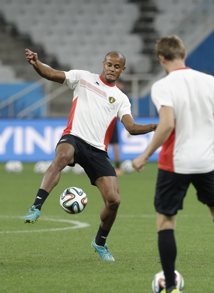 Photo - Belgium national soccer team player Vincent Kompany dribbles during an official training session the day before the group H World Cup soccer match between South Korea and Belgium at the Itaquerao Stadium in Sao Paulo, Brazil, Wednesday, June 25, 2014. (AP Photo/Lee Jin-man)