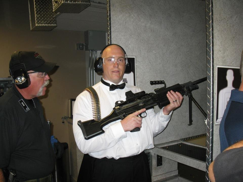 Photo - This July 28, 2012 photo provided by Bob MacDuff shows MacDuff holding an automatic weapon at the Gun store in Las Vegas after his