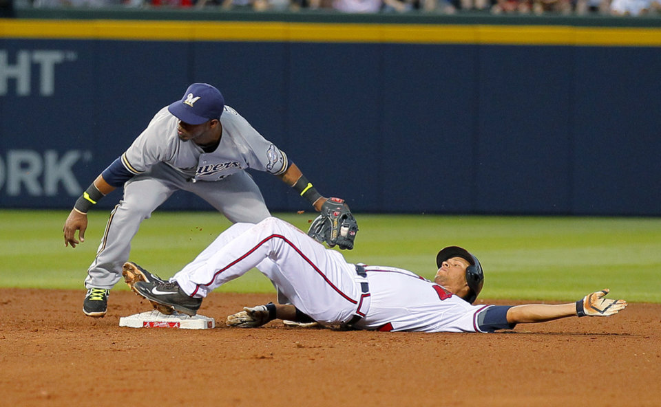 Photo - Milwaukee Brewers shortstop Jean Segura applies the tag as Atlanta Braves Andrelton Simmons runs to second base after his single in the fourth inning of a baseball game on Tuesday, May 20, 2014, in Atlanta. Simmons was originally called out on the play, but the call was overturned after a challenge. (AP Photo/Todd Kirkland)