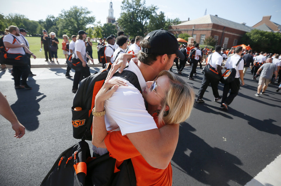 Photo -  OSU quarterback Taylor Cornelius hugs his mother, Phyllis Cornelius, before Thursday's win over Missouri State.