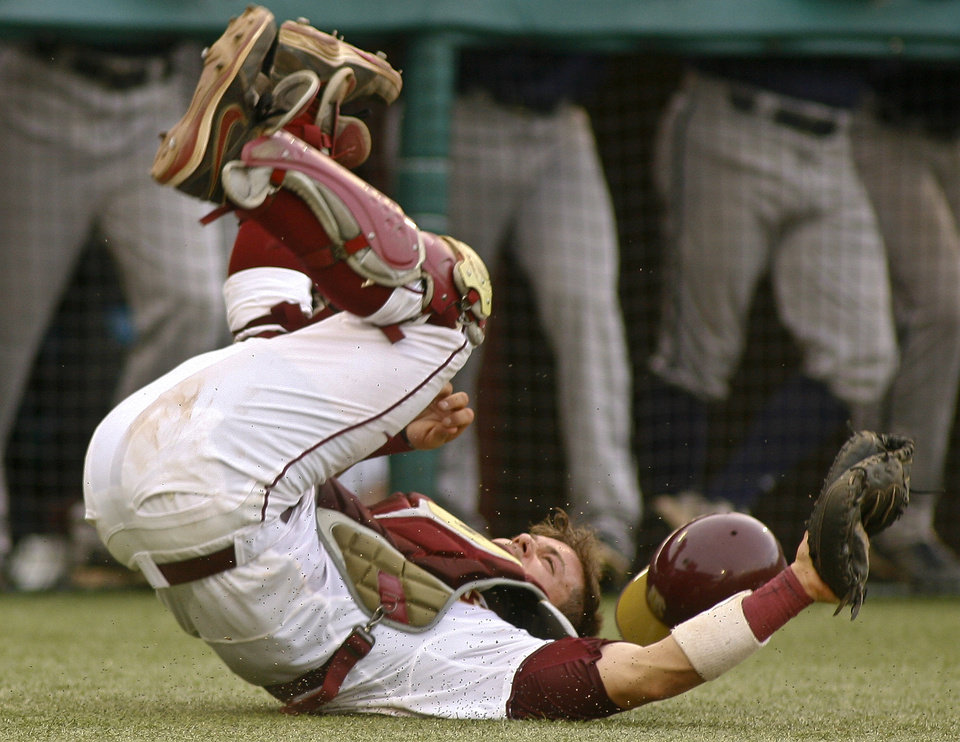 Photo - Florida State's Danny De La Calle tumbles, but holds on to a popped-up bunt for an out in the fifth inning of an NCAA college baseball tournament regionalgame against Georgia Southern on Friday, May 30, 2014 in Tallahassee, Fla. (AP Photo/Phil Sears)