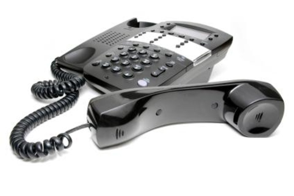 Photo - PHONE: Modern black business office telephone with the receiver off the hook isolated on a white background ORG XMIT: 1003051928163599