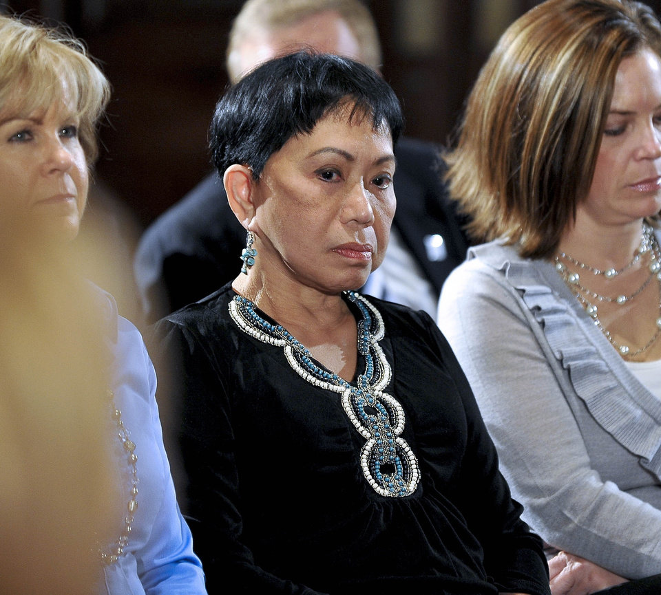 Photo - Kultida Woods listens to her son Tiger Woods making a statement at the Sawgrass Players Club, Friday, Feb. 19, 2010, in Ponte Vedra Beach, Fla. (AP Photo/Lori Moffett, Pool)  ORG XMIT: TWP111