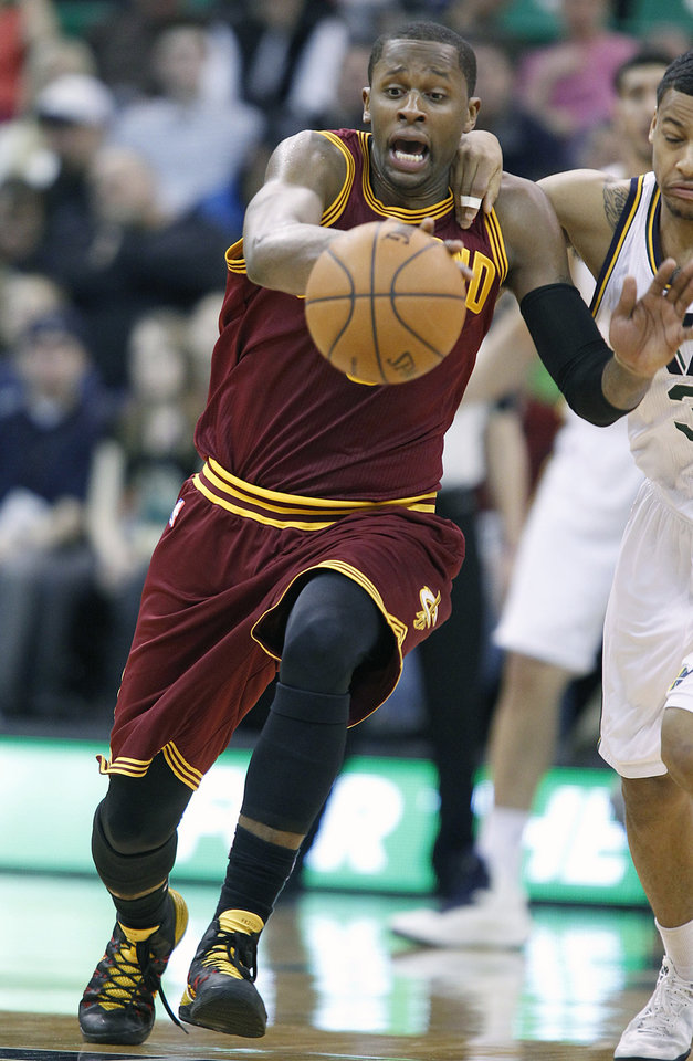 Photo - Cleveland Cavaliers C.J. Miles, left, steals the ball from Utah Jazz's Trey Burke during the first half of an NBA basketball game in Salt Lake City, Friday, Jan. 10, 2014. (AP photo/George Frey)