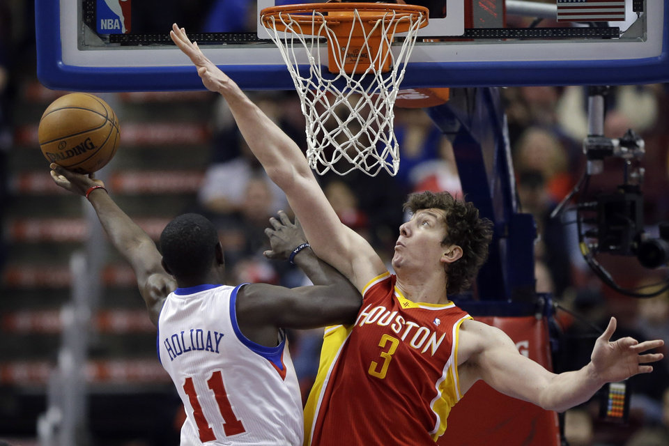 Philadelphia 76ers' Jrue Holiday, left, goes up for a shot against Houston Rockets' Omer Asik, of Turkey, in the first half of an NBA basketball game, Saturday, Jan. 12, 2013, in Philadelphia. (AP Photo/Matt Slocum)