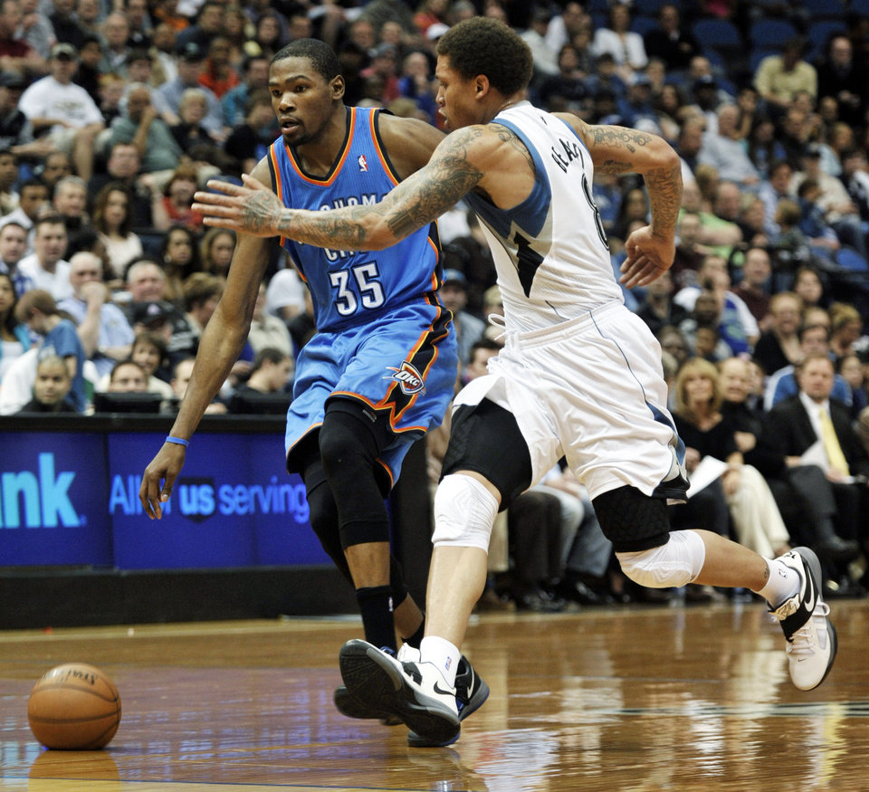 Photo - Oklahoma City Thunder's Kevin Durant, left, attempts to drive around Minnesota Timberwolves' Michael Beasley, right, in the second quarter of an NBA basketball game, Saturday, April 14, 2012, in Minneapolis. (AP Photo/Tom Olmscheid) ORG XMIT: MNTO102