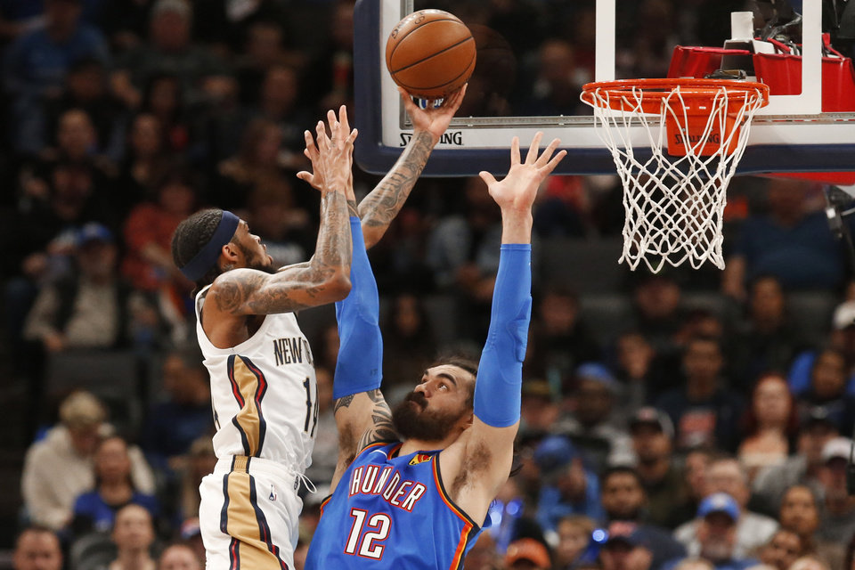 Photo - New Orleans Pelicans forward Brandon Ingram (14) goes up for a shot over Oklahoma City Thunder center Steven Adams (12) during the first half of an NBA basketball game Friday, Nov. 29, 2019, in Oklahoma City. [AP Photo/Sue Ogrocki]