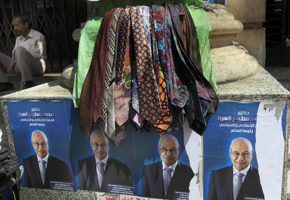 """An Egyptian street vendor displays ties over posters of Presidential candidate Selim el-Awa for the upcoming elections in Cairo, Egypt, Thursday, April 26, 2012. Egypt's election commission announced the final list of candidates this week for next month's presidential elections. Arabic on the posters read, """"Selim el-Awa for Egyptian Presidency."""" (AP Photo/Amr Nabil)"""