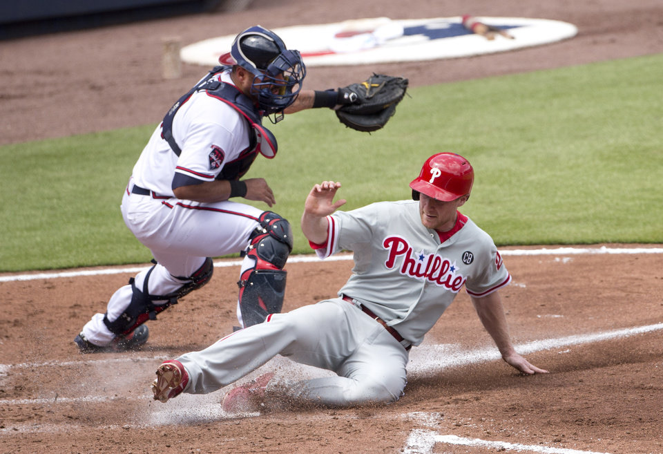 Photo - Philadelphia Phillies' Cody Asche (25) scores on a Ben Revere sacrifice fly as Atlanta Braves catcher Gerald Laird (11) handles the late throw in the third inning of a baseball game Monday, Sept. 1, 2014, in Atlanta. (AP Photo/John Bazemore)