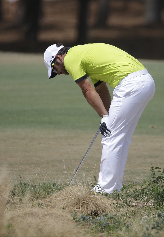 Photo - Paul Casey, of England, reacts after his shot out of the native area on the 18th hole during the first round of the U.S. Open golf tournament in Pinehurst, N.C., Thursday, June 12, 2014. (AP Photo/David Goldman)