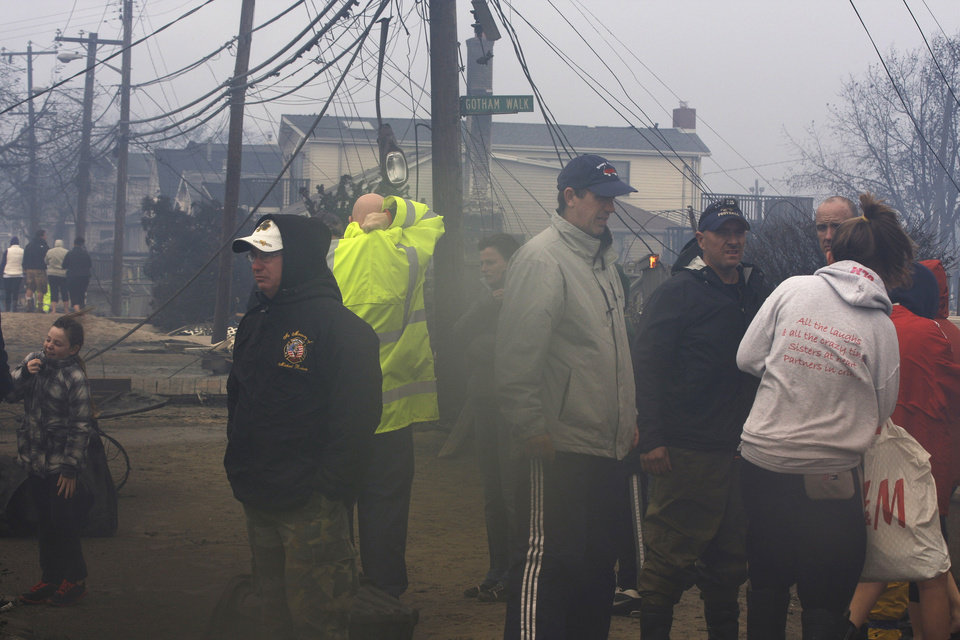 Photo -   People assess damage caused by a fire at Breezy Point in the New York City borough of Queens Tuesday, Oct. 30, 2012. The fire destroyed between 80 and 100 houses Monday night in an area flooded by the superstorm that began sweeping through earlier. (AP Photo/Frank Franklin II)