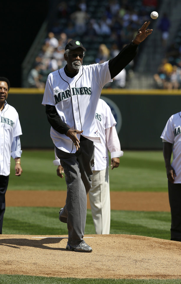 Photo - NBA bassketball great and former Boston Celtics center Bill Russell throws out the ceremonial first pitch of a baseball game between the Milwaukee Brewers and the Seattle Mariners, Sunday, Aug. 11, 2013, in Seattle. (AP Photo/Ted S. Warren)