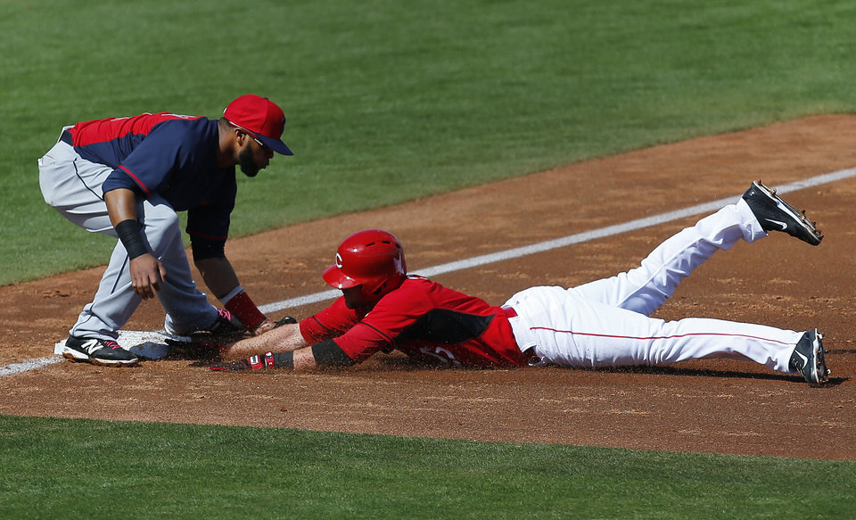 Photo - Cleveland Indians third baseman Carlos Santana, left, tags out Cincinnati Reds' Zack Cozart who was trying for triple in the second inning of an exhibition baseball game in Goodyear, Ariz., Thursday, Feb. 27, 2014. (AP Photo/Paul Sancya)