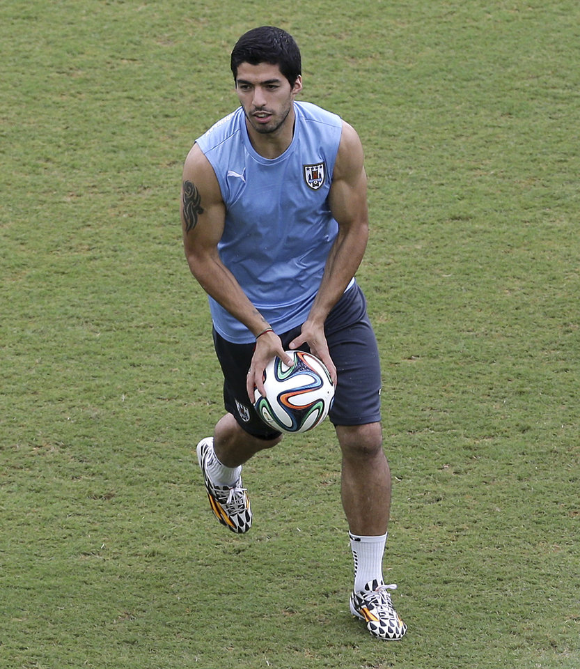 Photo - Uruguay's Luis Suarez runs on the pitch with a ball, during a training session the day before the team's next group D World Cup soccer match, at the Arena das Dunas in Natal, Brazil, Monday, June 23, 2014. (AP Photo/Antonio Clanni)