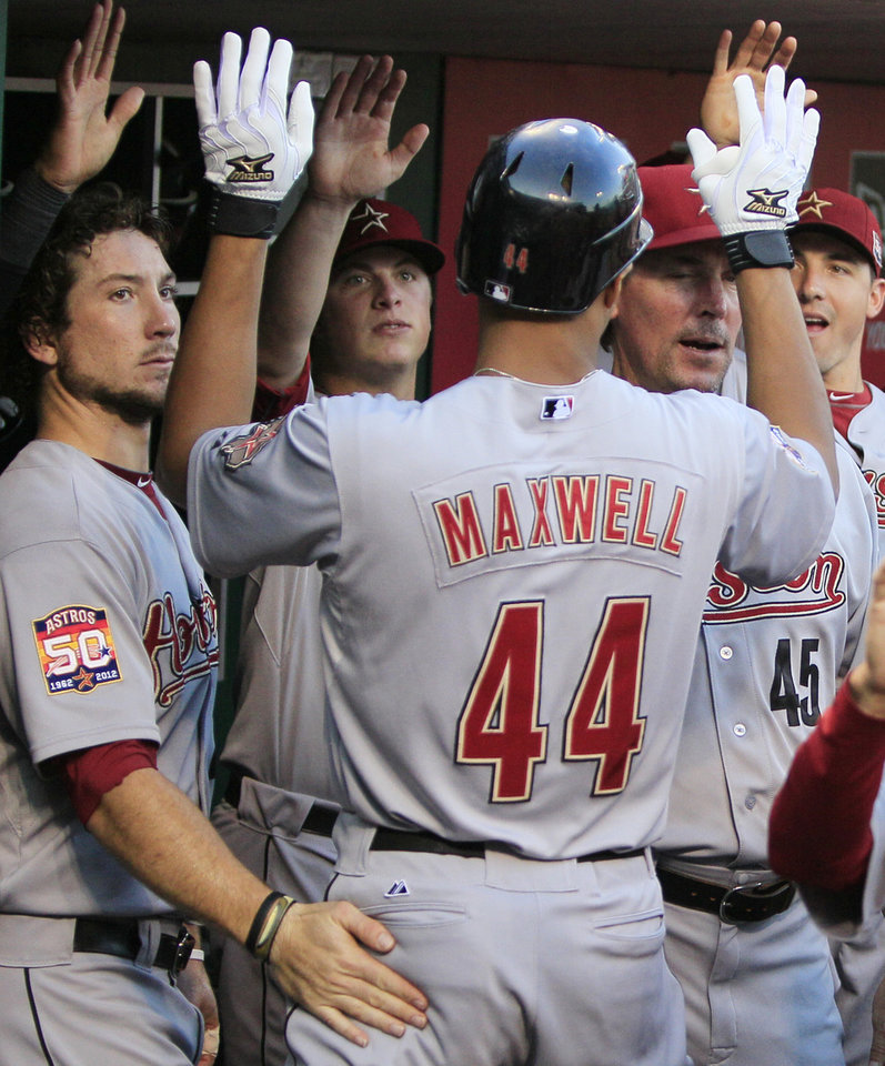 Photo -   Houston Astros' Justin Maxwell (44) celebrates in the dugout after hitting a two-run home run in the first inning of a baseball game against the Cincinnati Reds, Friday, Sept. 7, 2012, in Cincinnati. (AP Photo/Al Behrman)