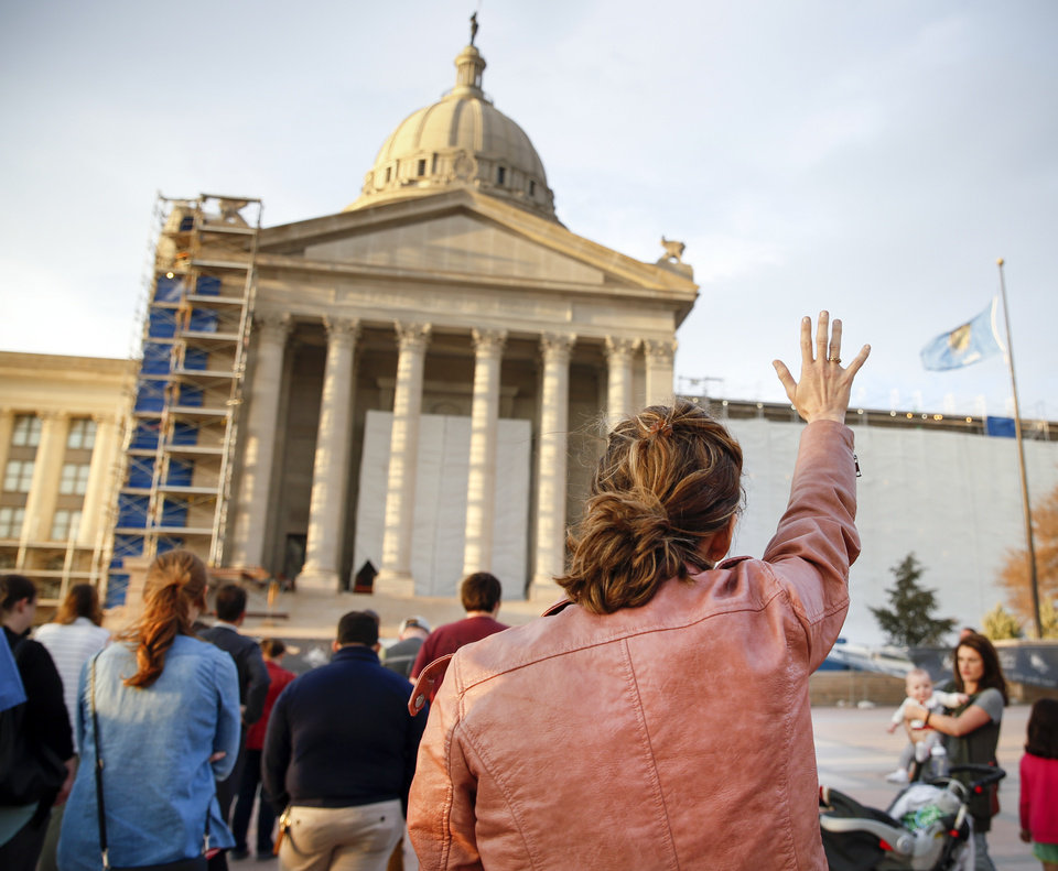 Photo - Ryan McLaughlin prays with others during the Churches for Teachers Prayer Vigil, an event supporting Oklahoma teachers and students, on the south side of the state Capitol in Oklahoma City, Thursday, March 15, 2018. Photo by Nate Billings, The Oklahoman