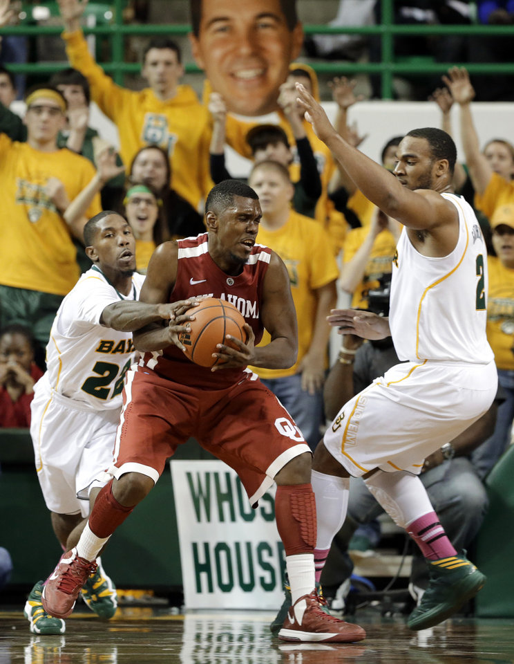 Photo - Baylor fans hold a large photo cut out of head coach Scott Drew, rear, as A.J. Walton, left, and Rico Gathers, right, defend against Oklahoma 's Andrew Fitzgerald, center, during the second half of an NCAA college basketball game Wednesday, Jan. 30, 2013, in Waco, Texas. Oklahoma won 74-71.  (AP Photo/Tony Gutierrez) ORG XMIT: TXTG113