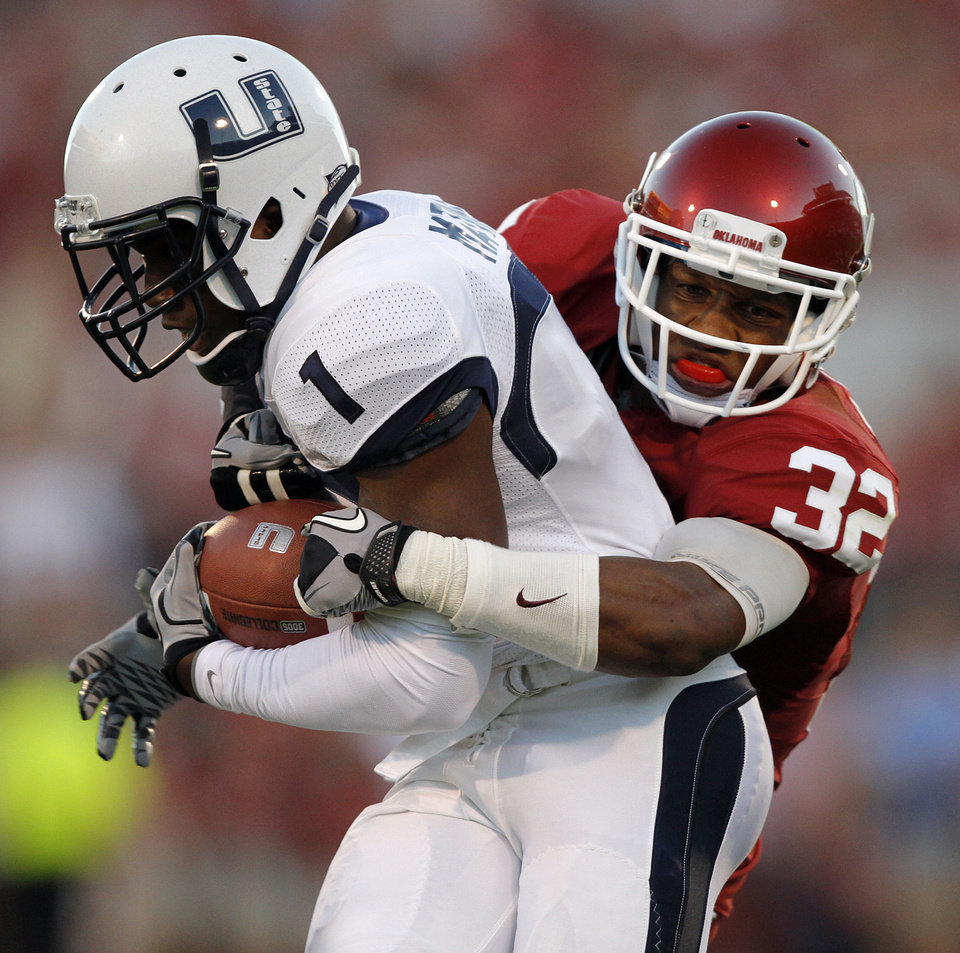 Photo - Oklahoma's Jamell Fleming (32) stops Utah State's Xavier Martin (1) during the first half of the college football game between the University of Oklahoma Sooners (OU) and Utah State University Aggies (USU) at the Gaylord Family-Oklahoma Memorial Stadium on Saturday, Sept. 4, 2010, in Norman, Okla.   Photo by Chris Landsberger, The Oklahoman