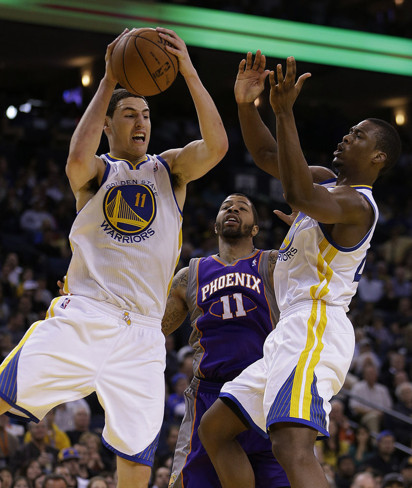 Golden State Warriors' Klay Thompson, left, rebounds over Phoenix Sun's Markieff Morris, center, as Warriors' Harrison Barnes, right, assists during the second half of an NBA basketball game Wednesday, Feb. 20, 2013, in Oakland, Calif. (AP Photo/Ben Margot)