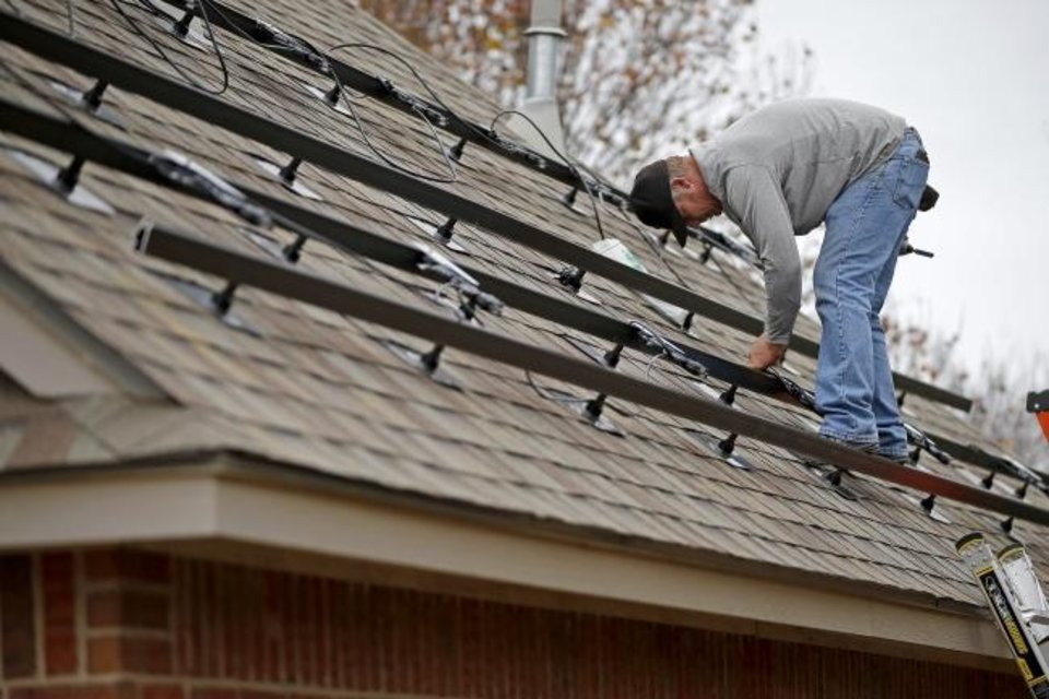 Photo -  Jeremy Rains, with Solar Power of Oklahoma, ties off wiring on brackets that will hold solar panels on the roof of Brian Bennett's home. [BRYAN TERRY/THE OKLAHOMAN]