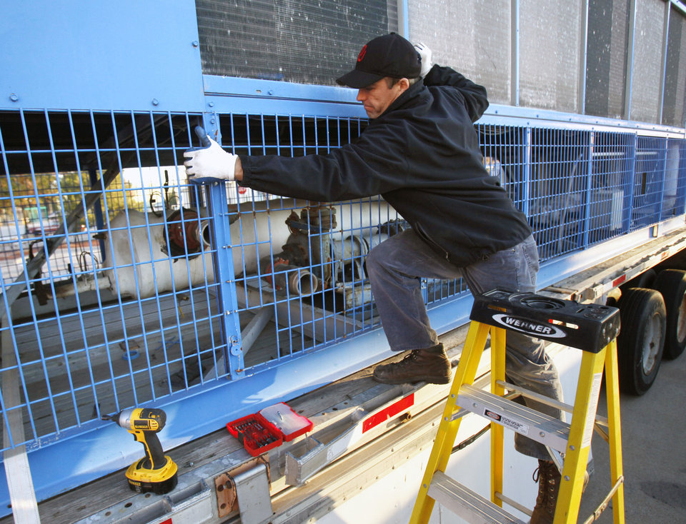 Dmitri Logoutine, owner of Ice Challenge Enterprises LLC and operator of the Edmond�s outdoor ice skating rink, prepares the refrigeration pumps and lines for the rink in Festival Market Place. PHOTOS BY PAUL HELLSTERN, THE OKLAHOMAN