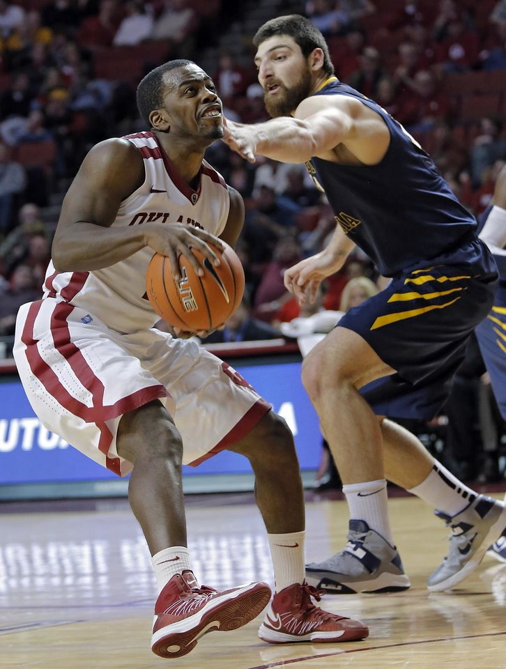Oklahoma's Sam Grooms (1) is hit in the face on his way to the basket by West Virginia 's Deniz Kilicli (13) during the second half of the college basketball game between the University of Oklahoma Sooners (OU) and the West Virginia University Mountaineers (WVU) at the Lloyd Noble Center on Wednesday, March 6, 2013, in Norman, Okla. Photo by Chris Landsberger, The Oklahoman