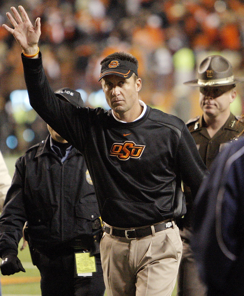 Photo - OSU head coach Mike Gundy waves to Cowboy fans after the college football game between the Oklahoma State University Cowboys (OSU) and the University of Texas Longhorns (UT) at Darrell K Royal-Texas Memorial Stadium in Austin, Texas, Saturday, November 13, 2010. OSU won, 33-16. Photo by Nate Billings, The Oklahoman