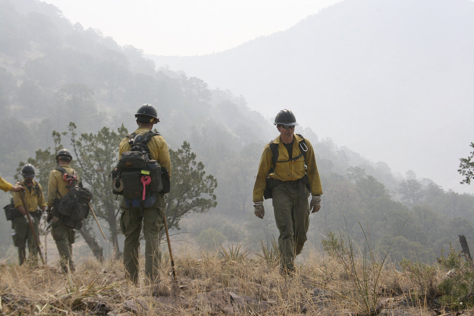 Photo -   Firefighters from the Granite Mountain Hotshots of Prescott, Ariz., cut a fire line along a mountain ridge outside Mogollon, N.M., on Saturday, June 2, 2012. The crew is part of an effort to manage and contain the Whitewater-Baldy fire which has burned more than 354 square miles of the Gila National Forest in New Mexico. (AP Photo/U.S. Forest Service, Tara Ross)