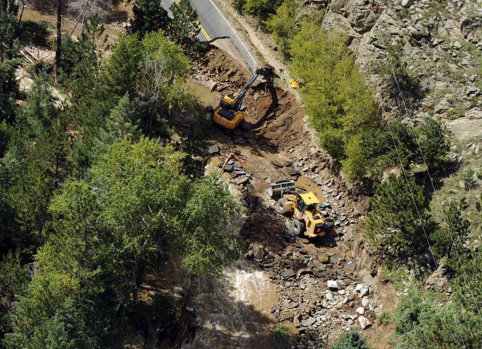 Photo - FILE- In this Sept. 17, 2013, file photo, heavy equipment works on a road damaged by flooding during a helicopter search of the area around Boulder, Colo.  Colorado transportation officials are scrambling to replace key mountain highways with at least gravel before the first winter storms hit as early as October, but rebuilding every flood-damaged road and bridge in the mountains and plains will have to wait until 2014 _ or beyond. (AP Photo/The Denver Post, Joe Amon, Pool)