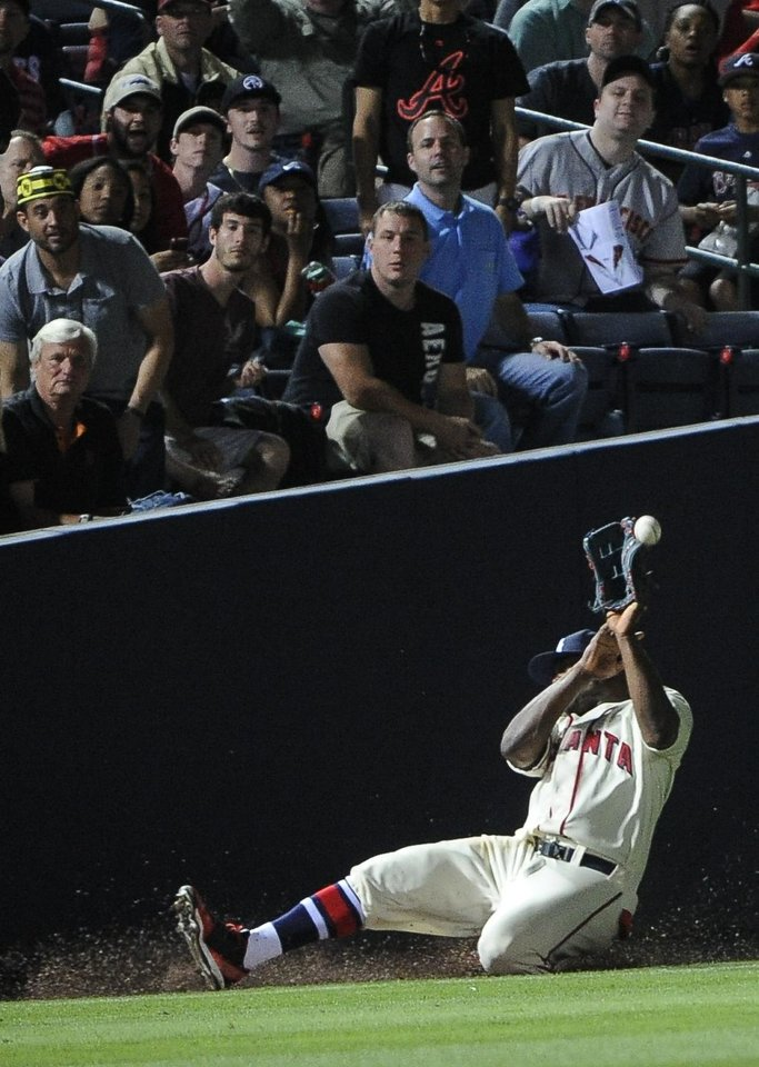 Photo - Atlanta Braves left fielder Justin Upton (8) can't keep a high fly foul ball in the glove off the bat of San Francisco Giants' Hunter Pence during the sixth inning of a baseball game, Saturday, May 3, 2014, in Atlanta. (AP Photo/John Amis)