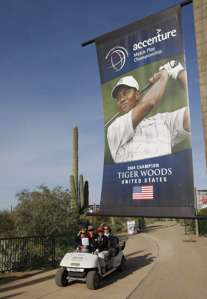 Photo - Volunteers drive below a poster of Tiger Woods as they arrive for work at the Accenture Match Play Championship golf tournament Friday, Feb. 19, 2010, in Marana, Ariz. Woods has apologized for having affairs and says he is unsure when he will return to competitive golf. Woods spoke for more than 13 minutes Friday, Feb. 19, 2010,  from the clubhouse at the TPC Sawgrass, home of the PGA Tour.  (AP Photo/Matt York) ORG XMIT: AZLI104