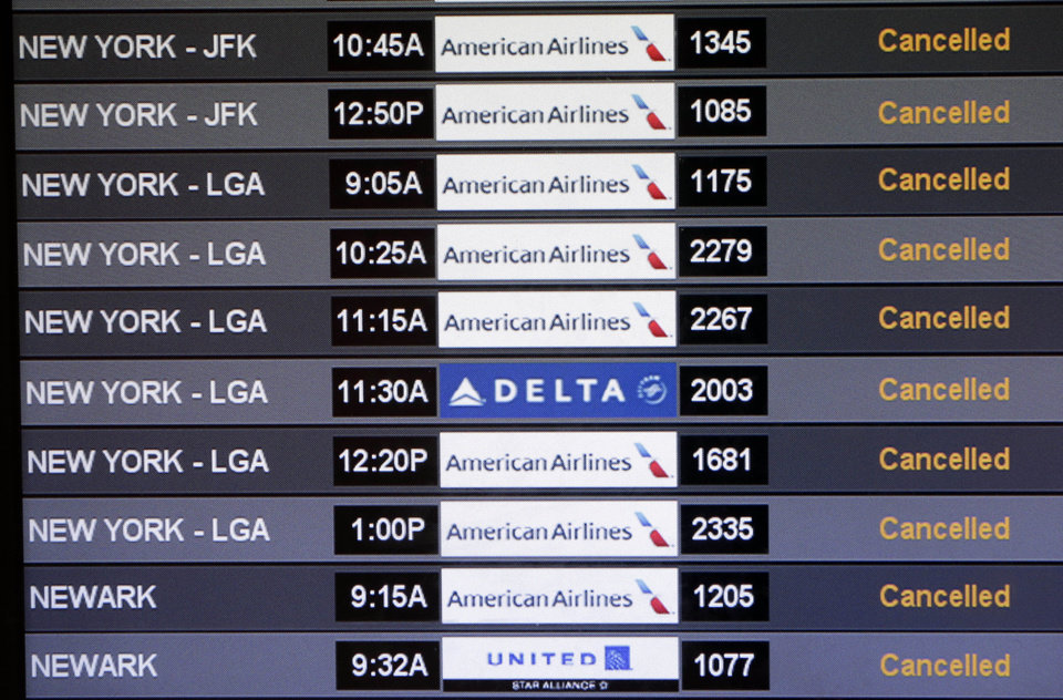Photo - A board listing departing flights shows cancellations to New York and Newark airports at Miami International Airport, Thursday, Feb. 13,  2014, in Miami. Some 5,000 flights have been cancelled Thursday due to bad weather in the south and northeast. (AP Photo/Lynne Sladky)