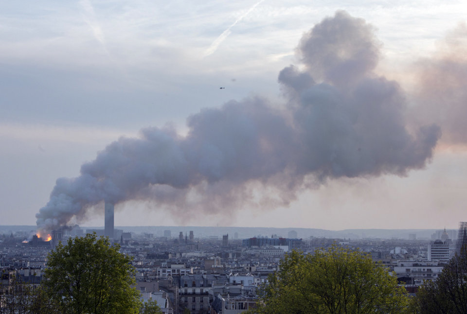 Photo - Notre Dame cathedral is burning in Paris, Monday, April 15, 2019. Massive plumes of yellow brown smoke is filling the air above Notre Dame Cathedral and ash is falling on tourists and others around the island that marks the center of Paris. (AP Photo/Rafael Yaghobzadeh)