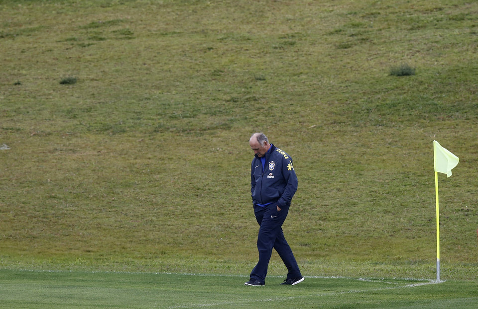 Photo - Brazil's coach Luiz Felipe Scolari walks on the pitch during practice at the Granja Comary training center in Teresopolis, Brazil, Friday, July 11, 2014. Brazil will face the Netherlands in the World Cup third-place match Saturday. (AP Photo/Leo Correa)