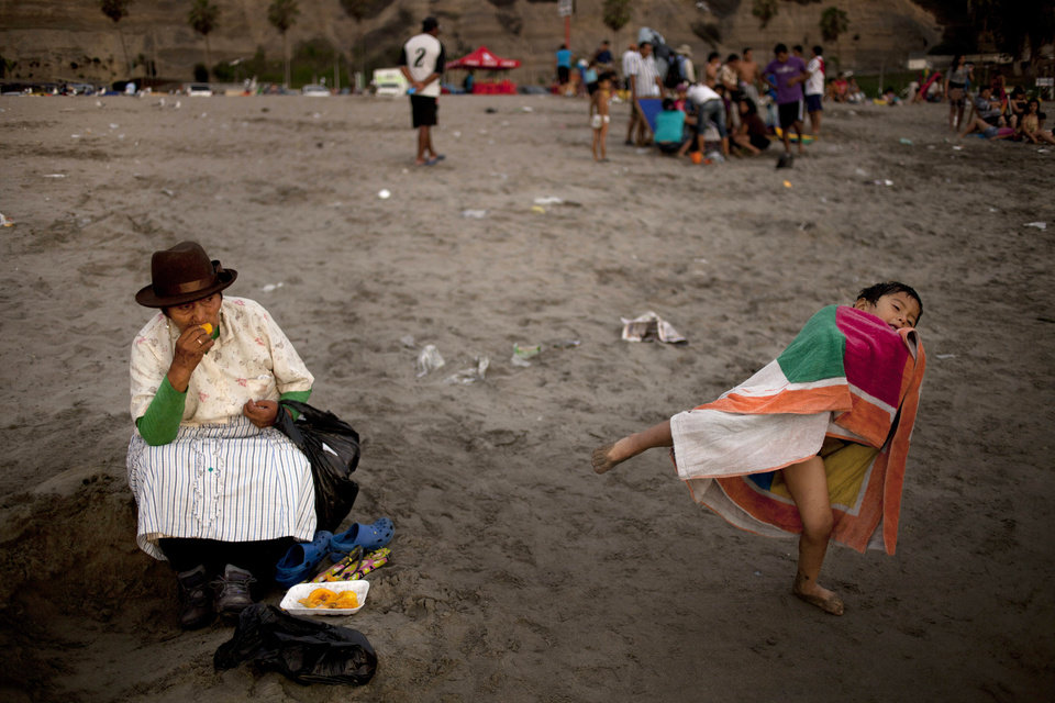 In this Jan. 18, 2013 photo, a woman snacks on mango fruit as her grandson plays nearby on Agua Dulce beach in Lima, Peru. While Lima's elite spends its summer weekends in gate beach enclaves south of the Peruvian capital, the working class jams by the thousands on a single municipal beach of grayish-brown sands and gentle waves. On some weekends during the Southern Hemisphere summer, which runs from December until March, as many as 40,000 people a day visit the half-mile-long (kilometer-long) strip of Agua Dulce.  (AP Photo/Rodrigo Abd)