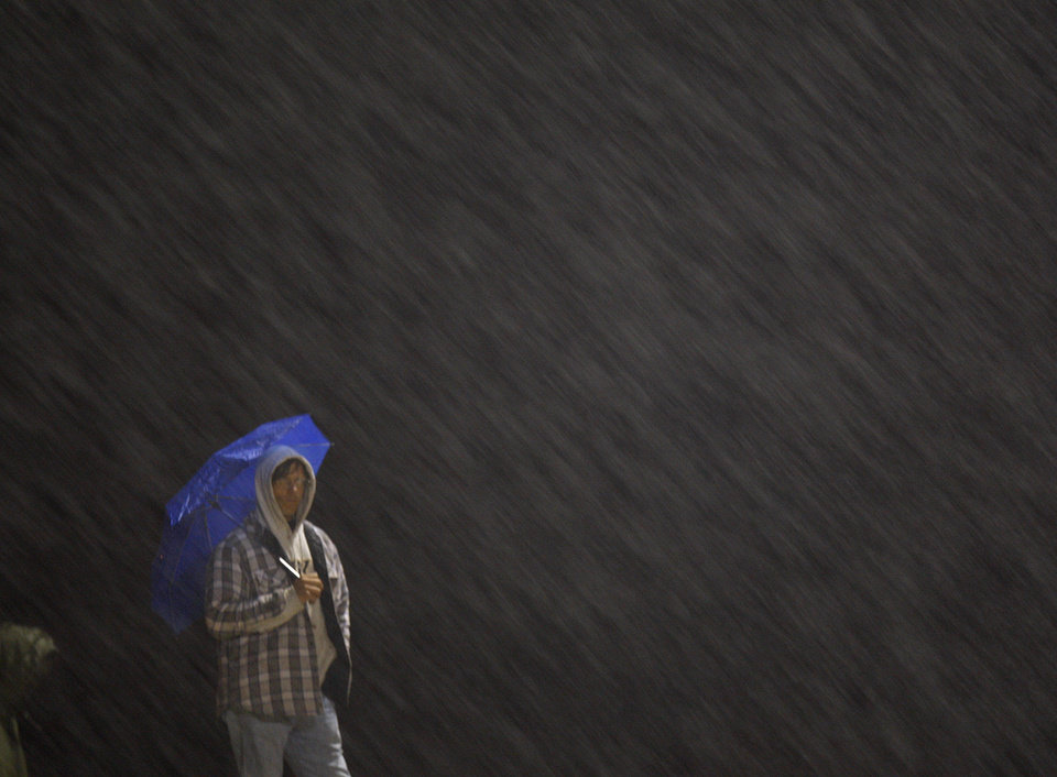 Photo - Standing in the rain, Millwood fan Mike Jorski watches the Class 2A high school football playoff game between Millwood and Lincoln Christian in Oklahoma City, Friday, Nov. 25, 2011. Photo by Bryan Terry, The Oklahoman