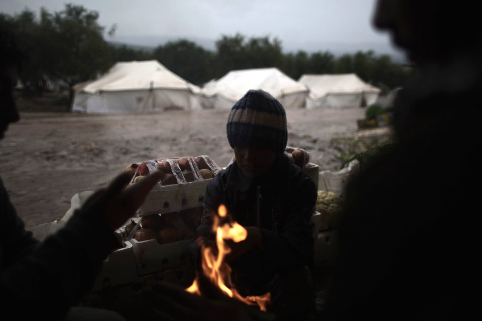 Photo - Syrians, who fled their homes with their families, gather around a fire to warm themselves at a makeshift vegetables store in a camp for the displaced in the village of Atmeh, Syria, Tuesday, Dec. 18, 2012. (AP Photo/Muhammed Muheisen)