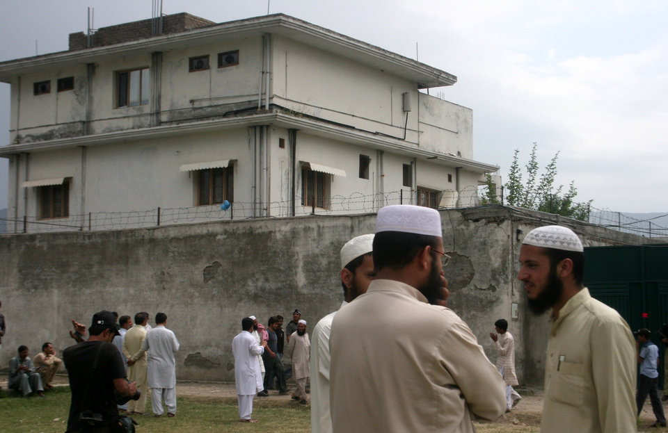 Photo -   FILE - In this May 5, 2011 file photo, local residents and media are seen outside the house where al-Qaida leader Osama bin Laden was caught and killed in Abbottabad, Pakistan. Local residents say Pakistan has started to demolish the compound in the northwest city of Abbottabad where Osama bin Laden lived for years and was killed by U.S. commandos. Two residents say the government brought in three mechanized backhoes Saturday, Feb. 25, 2012, and began destroying the tall outer walls of the compound after sunset. They set up floodlights to carry out the work. (AP Photo/Aqeel Ahmed, File)