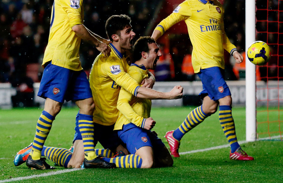 Photo - Arsenal's Santi Cazorla, center right, celebrates his goal with teammate Olivier Giroud, center left, during the English Premier League soccer match between Southampton and Arsenal at St Mary's stadium in Southampton, England, Tuesday, Jan. 28, 2014.  (AP Photo/Matt Dunham)