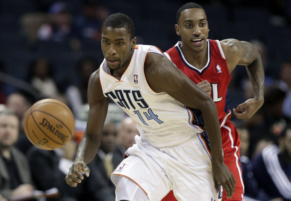 Charlotte Bobcats' Michael Kidd-Gilchrist, front, and Atlanta Hawks' Jeff Teague, rear, chase a loose ball during the first half of an NBA basketball game in Charlotte, N.C., Wednesday, Jan. 23, 2013. (AP Photo/Chuck Burton)