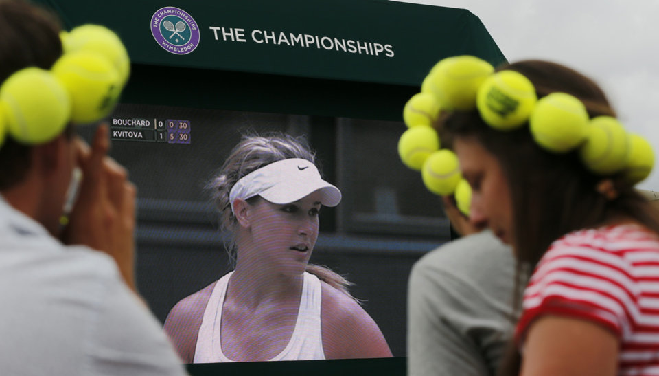 Photo - Spectators watch Eugenie Bouchard of Canada on a large video screen as she is defeated by Petra Kvitova of Czech Republic in the women's singles final against Eugenie Bouchard of Canada at the All England Lawn Tennis Championships in Wimbledon, London Saturday, July 5, 2014. (AP Photo/Ben Curtis)