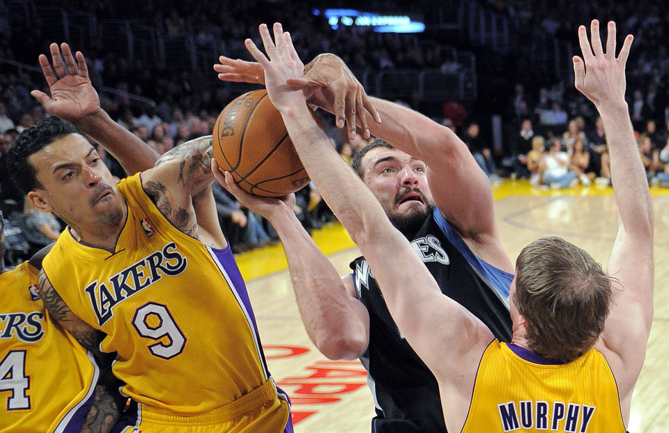 Minnesota Timberwolves center Nikola Pekovic, center, of Montenegro puts up a shot as Los Angeles Lakers forward Matt Barnes, left, and forward Troy Murphy defend during the first half of an NBA basketball game, Wednesday, Feb. 29, 2012, in Los Angeles. (AP Photo/Mark J. Terrill)