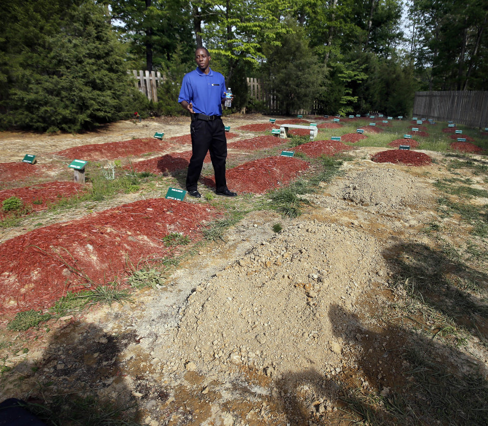 Bukhari Abdel-Alim, of Islamic Funeral Services of Virginia, talks to reporters near two newly dug graves at the Doswell, Va. cemetery where Boston Marathon bombing suspect Tamerlan Tsarnaev is buried, Friday, May 10, 2013. Ruslan Tsarni, the uncle of Tamerlan Tsarnaev, said his nephew was buried in the cemetery north of Richmond.  Tsarnaev was killed April 19 in a getaway attempt after a gun battle with police. His younger brother, Dzhokhar, was captured later and remains in custody. It is unknown which grave contains Tsarnaev's remains. (AP Photo/Richmond Times-Dispatch, Joe Mahoney)