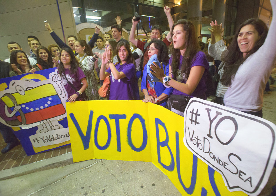 Venezuelan citizens living in the United States including Vanessa Dunn, holding Venezuela flag sign, Lia Nunes, holding Voto (Vote) sign, and Joyce Sosa clapping over Bus sign, all from Miami, Florida wait in line to vote at the New Orleans Ernest Morial Convention Center, in New Orleans, Sunday, Oct. 7, 2012. Hundreds of Venezuelans living in the U.S. streamed into New Orleans on Sunday to cast ballots in the presidential election in their homeland, many of them determined to end the 13-year reign of Hugo Chavez. With the country's consulate in Miami closed, thousands of Venezuelans traveled by bus, car and plane to cast their votes at the consulate in New Orleans. (AP Photo/Matthew Hinton)