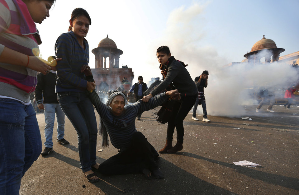 Protesters help an injured man as they run away from tear gas fired by Indian police while they are driven back from North Block near the Presidential Palace in New Delhi, India, Saturday, Dec. 22, 2012. Police used tear gas and water cannons to push back thousands of people who tried to march to the presidential mansion to protest the recent gang rape and brutal beating of a 23-year-old student on a moving bus. (AP Photo/Saurabh Das)