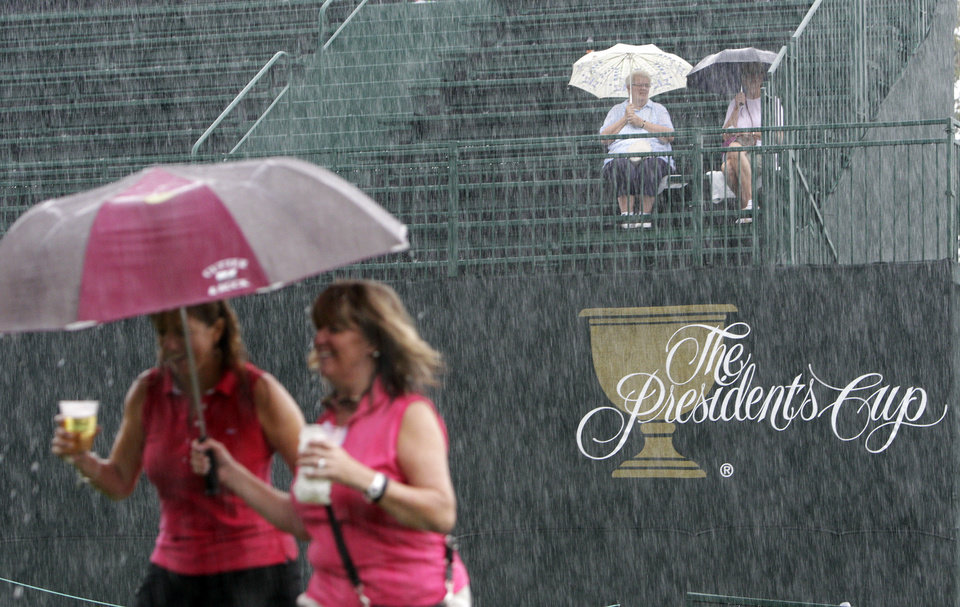 Photo - Fans brave the rain during a weather delay at the Presidents Cup golf tournament at Muirfield Village Golf Club Friday, Oct. 4, 2013, in Dublin, Ohio. (AP Photo/Jay LaPrete)